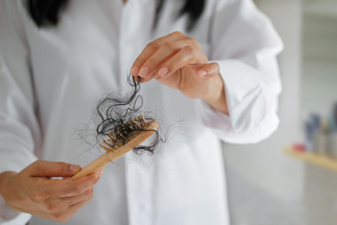 woman taking hair off a brush