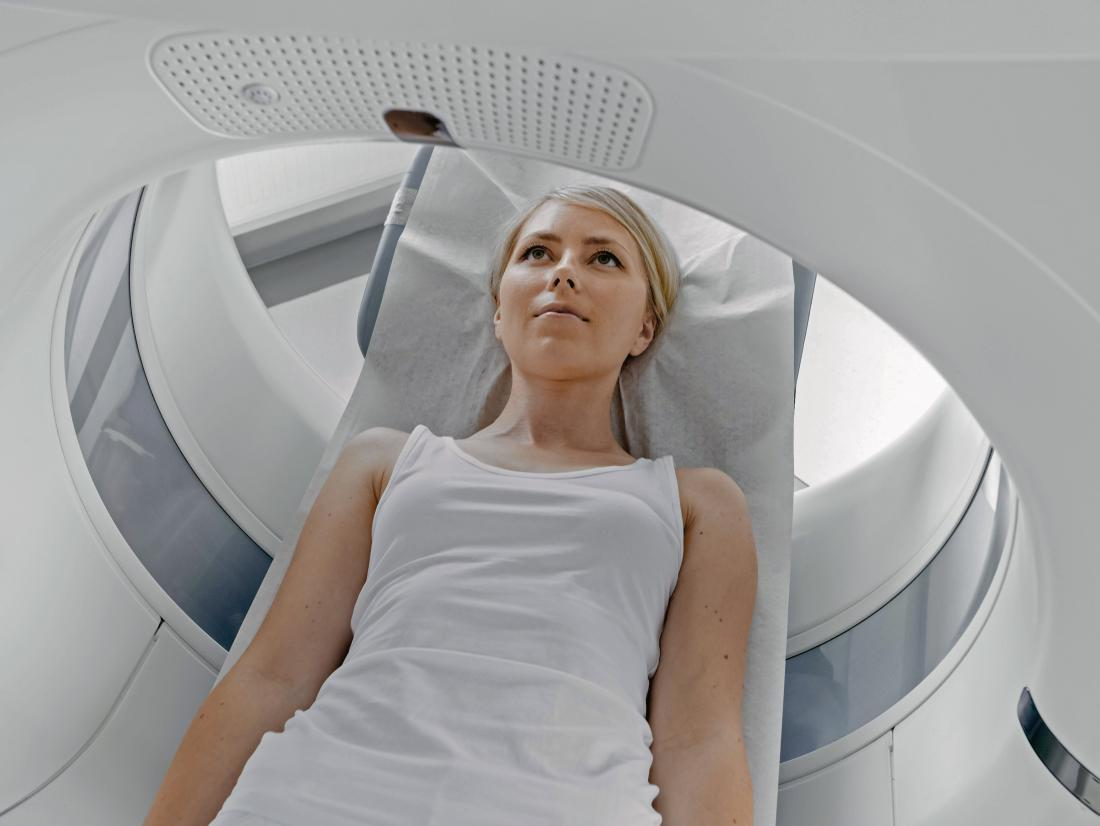 a woman lying down on during a CT scan or MRI