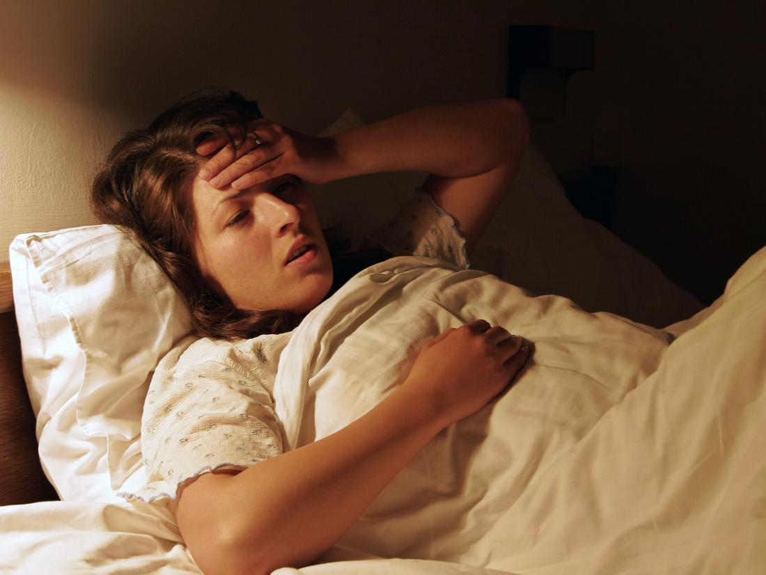 a woman with a headache at night.